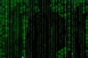 Illustration of a cyber criminal's silhouette masked behind a stream of 1s and 0s