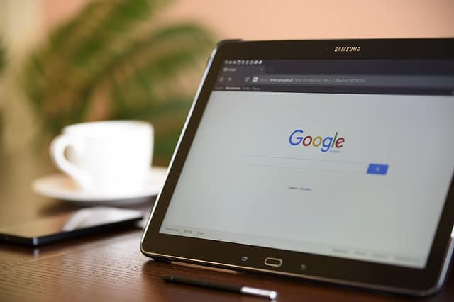 Folding tablet standing on table with Google search engine displayed