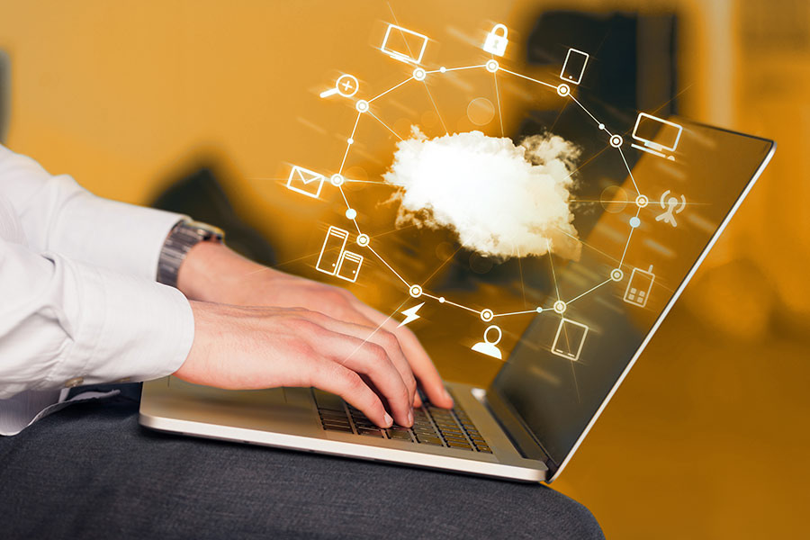 Man using laptop with cloud services graphic