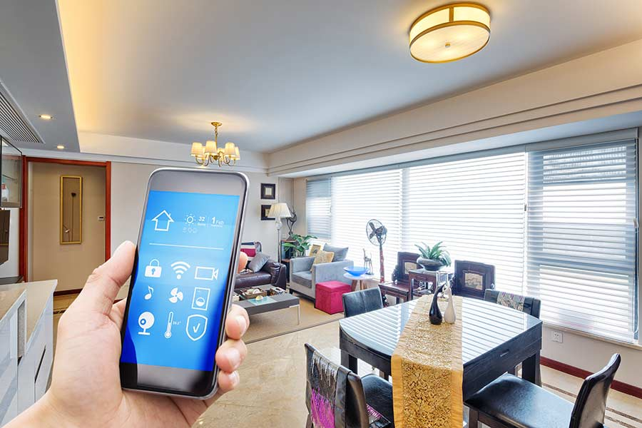 Hand holding a phone with apps to connect to several smart devices in a home