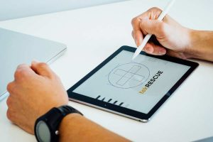 Graphic designer creating a vector logo on a tablet